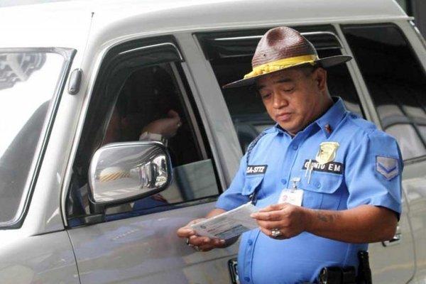 Filipino police officer checking on a driving w/out license case