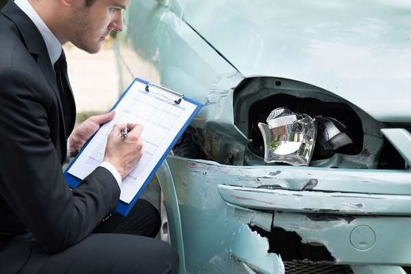 insurance agent inspecting a damaged car