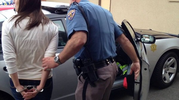 Handcuffed woman with a police officer