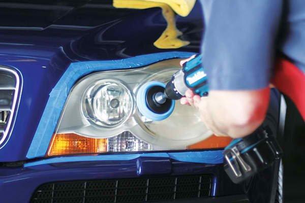 An expert cleaning the headlights