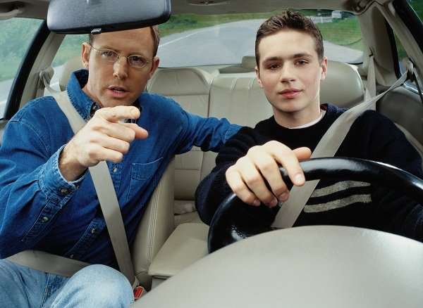 Man teaching the boy how to drive