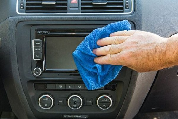 Man cleaning the infotainment touchscreen