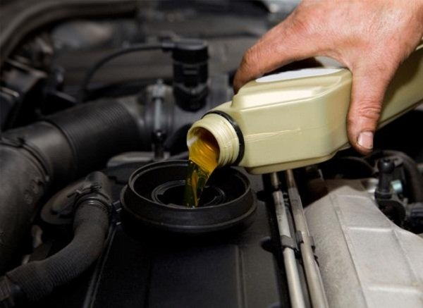 Man pouring engine oil
