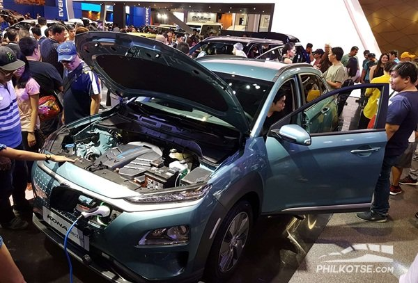 A picture of the Hyundai Kona Electric with an open hood and charger attached