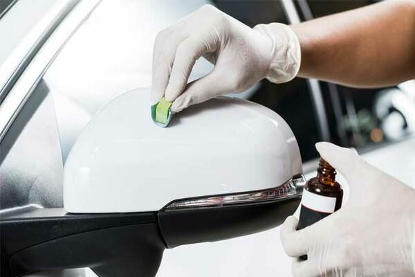 Man applying paint protection to cars