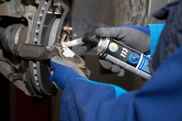Man applying damping paste on the brake pads
