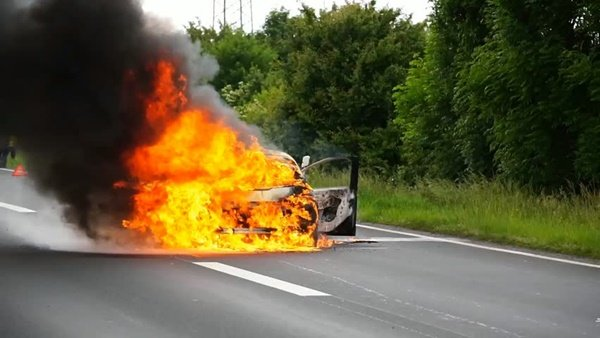 Car burning on road