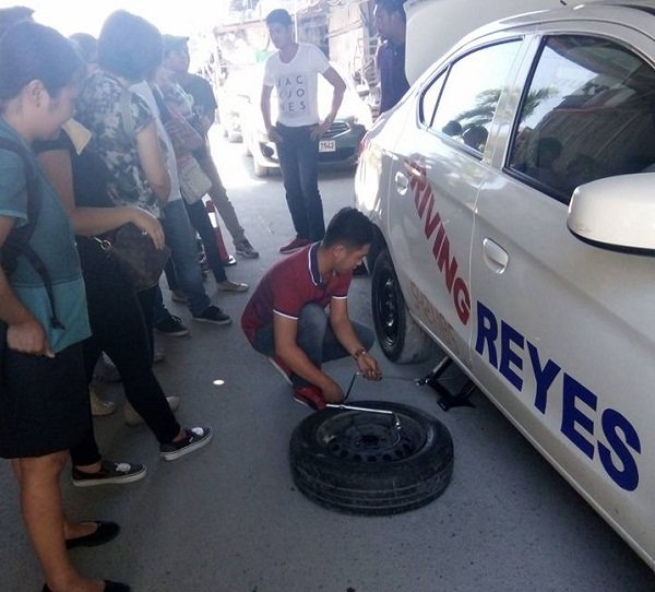 A picture of a Reyes Driving Institute instructor demonstrating how to change a tire
