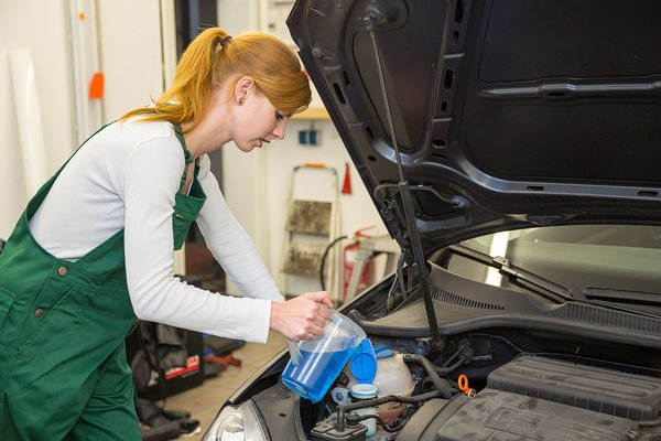 Woman putting engine coolant in the engine coolant reservoir