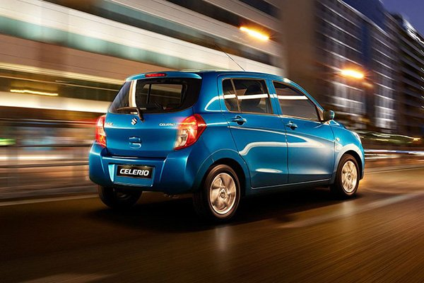 A picture of a Suzuki Celerio travelling in the city at night