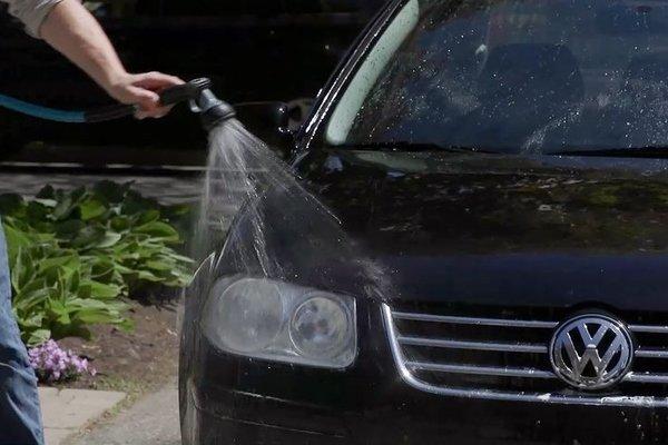Rinsing car exterior thoroughly using a hose
