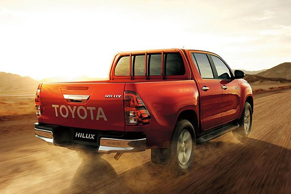 A 2019 Toyota Hilux running on a desert into the sunset