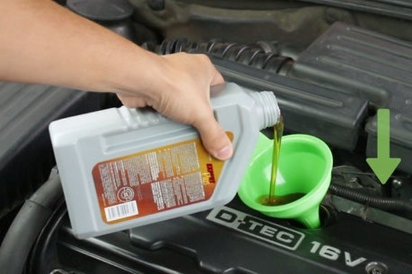 man putting engine oil in the car