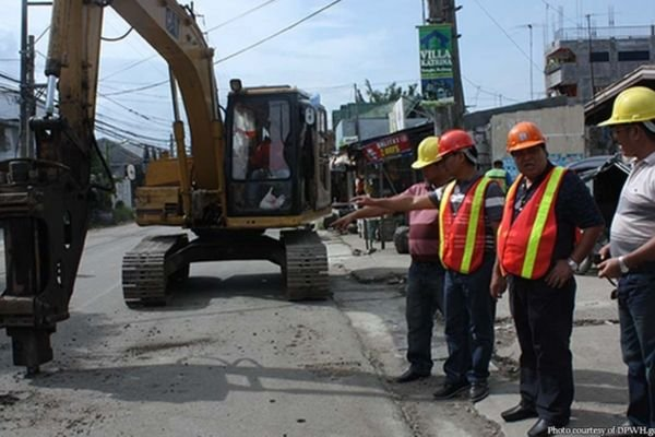 A picture of DPWH personnel inspecting a road in the midst of repair