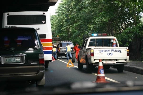 A picture of an SLEX patrol assisting a motorist