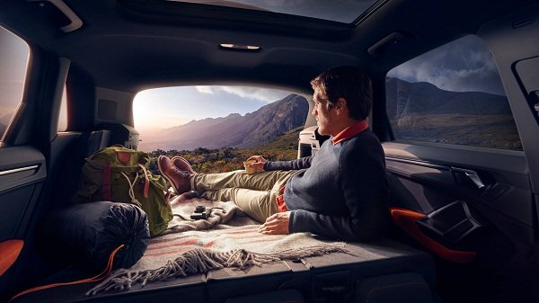 A picture of a man lying down inside the 2020 Audi Q3's trunk