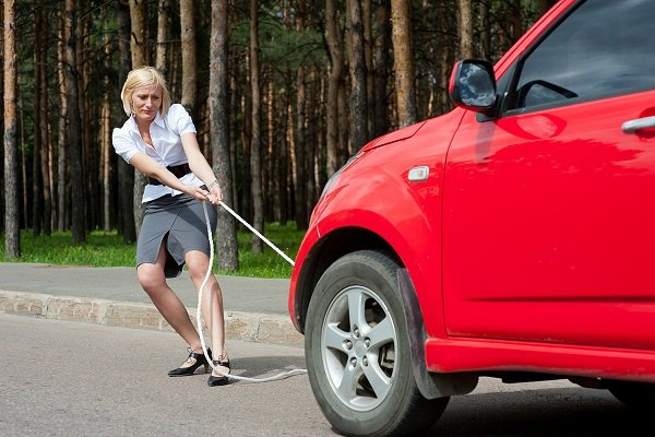 A picture of a woman getting frustrated at her car that won't start