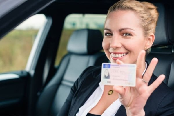 A picture of a driver showing her license.