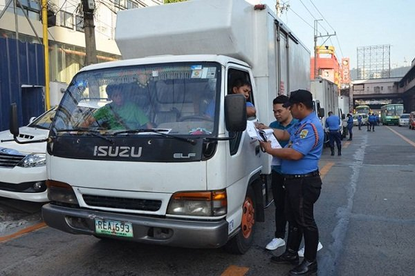 A picture of an MMDA enforcer issuing a ticket to a truck