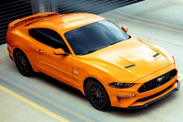 A picture of an orange Ford Mustang GT.