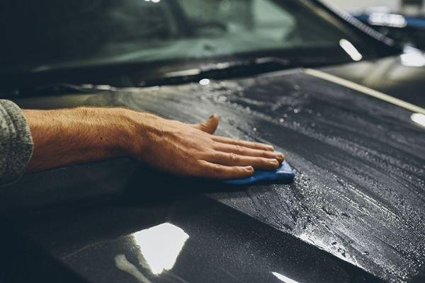 A guy applying car clay