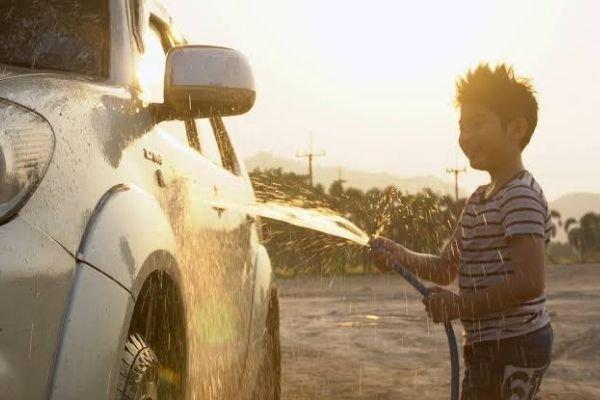A boy washing a car