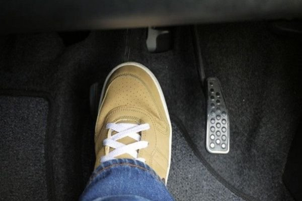 A picture of a foot pressing on a brake pedal
