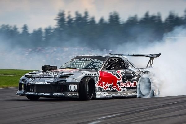 A picture of a Mazda RX-7 drift car performing a drift