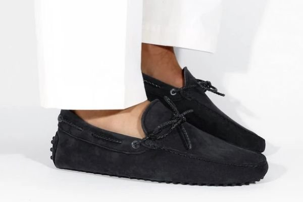 A picture of a person wearing dark colored loafers