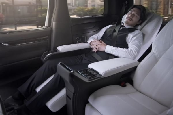 A picture of a man sleeping inside the Lexus LM