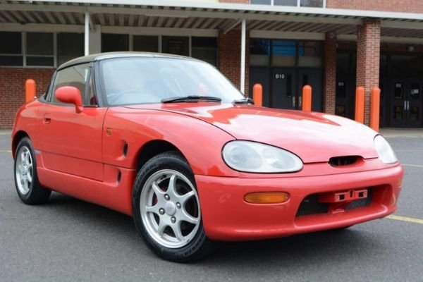 A picture of a red Suzuki Cappuccino parked on a lot