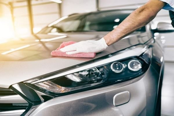 A picture of a guy waxing his car