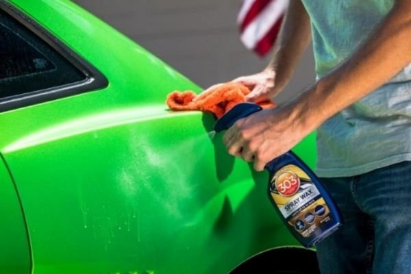 A picture of a man apply a spray on wax