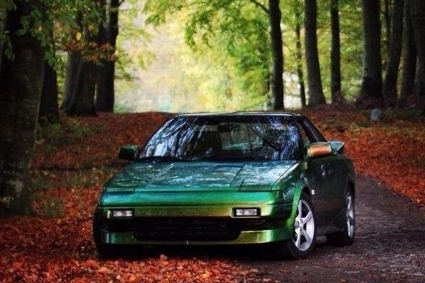 A picture of a green Toyota MR2 in the woods