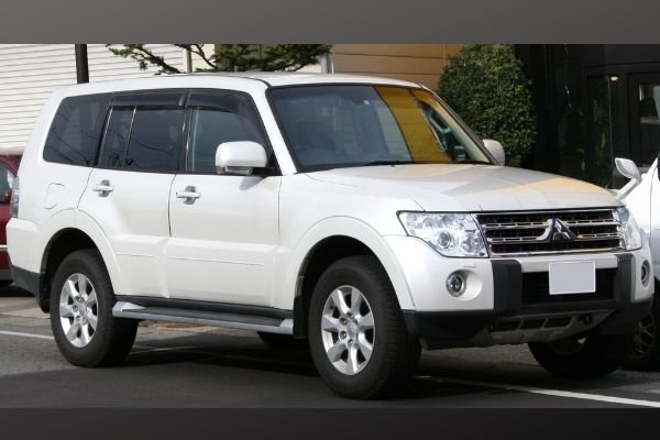 A picture of a white Mitsubishi Pajero parked on the side of a road