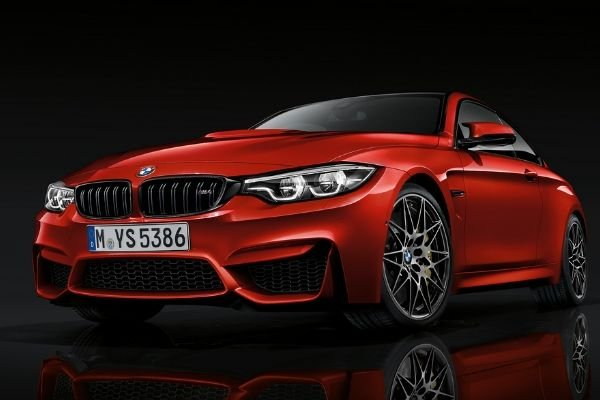 A picture of a red BMW M4 with a black background