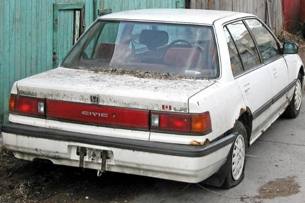 A picture of a white beater honda rotting in the garage