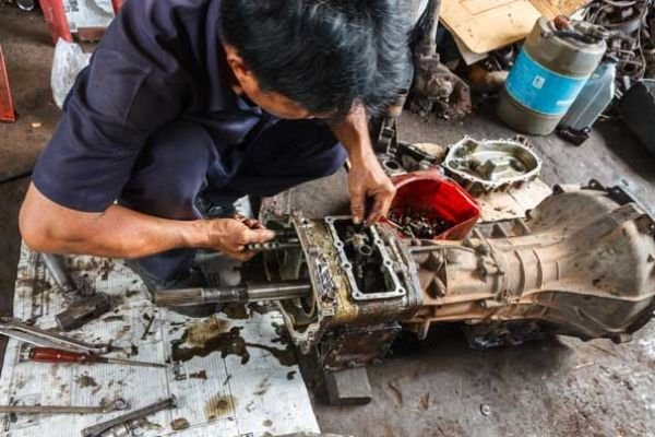 A picture of a man repairing a transmission