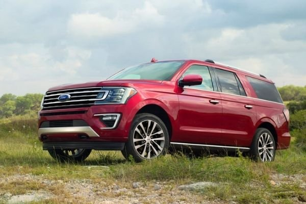 A picture of a red Ford Expedition climbing a hill