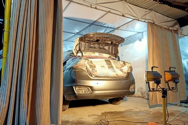 A picture of Cars 101's shop with a car mid-paint job