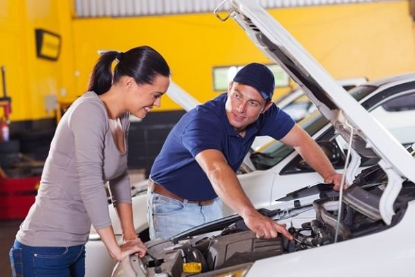 A picture of a woman and a car mechanic