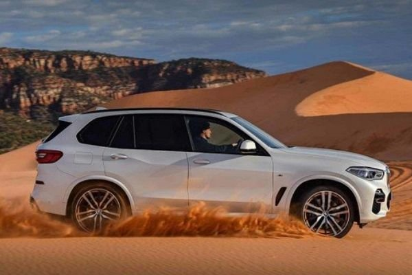 A picture of the 2020 BMW X5 driving on sand