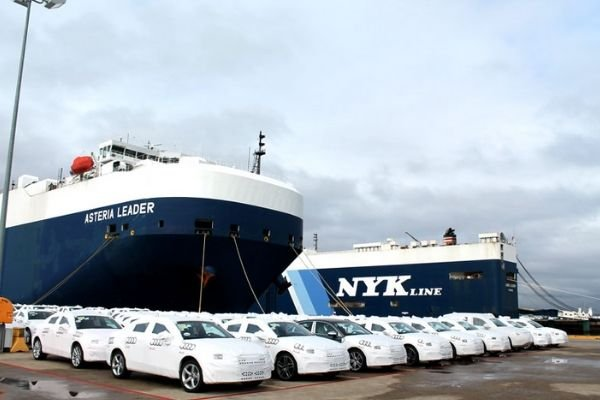 A picture brand new cars about to be loaded into a car carrier ship