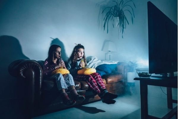 Two girls watching a tv at night