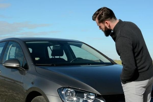 A picture of a man looking at his car