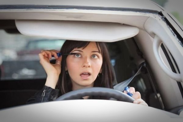 A picture of a young woman putting on makeup while driving