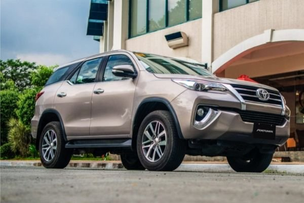 A picture of the Toyota Fortuner near a fancy building
