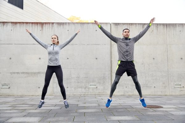 Two people doing jumping jacks