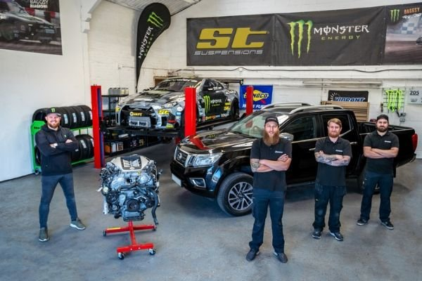 The SBMotorsport staff posing with a GT-R engine and the base Navara