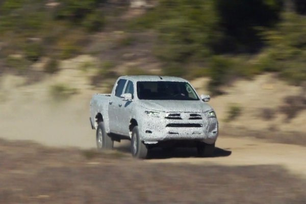 A camouflaged Hilux doing rally runs